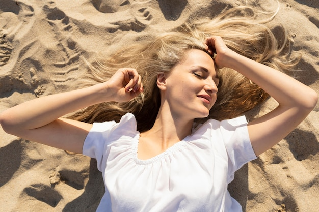 Top view of woman posing on beach sand Free Photo