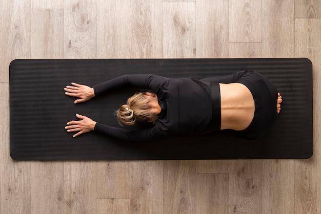 Вид сверху женщина, практикующая йогу Бесплатные Фотографии
