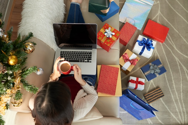 Top view of woman seated on the sofawith laptop and coffee surrounded by numerous gift boxes Free Photo