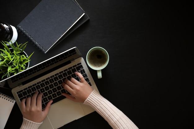 Top view woman using laptop on dark leather workspace desk Premium Photo