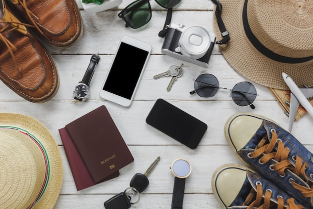 トップビューの女性と男性のaccessoires旅行コンセプト。白と黒の携帯電話、飛行機、帽子、パスポート、腕時計、サングラス、靴と木製テーブルのキー。 無料写真