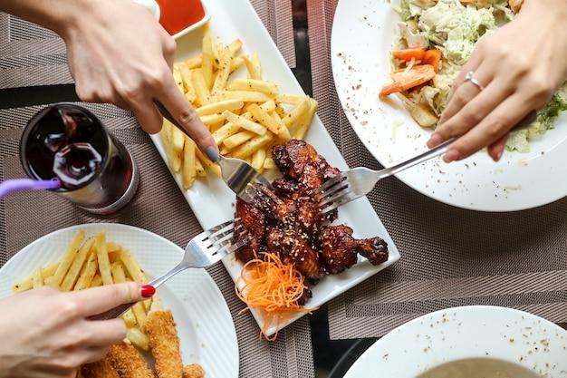 Donne di vista superiore che mangiano le ali di pollo del barbecue con le fritture e l'insalata con succo sul tavolo Foto Gratuite