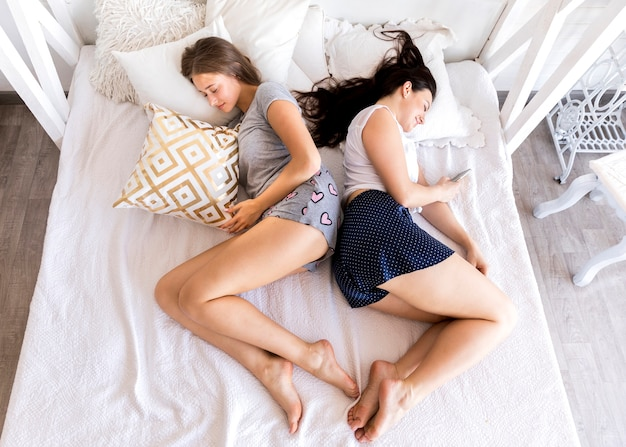 Top view women sleeping back to back Free Photo