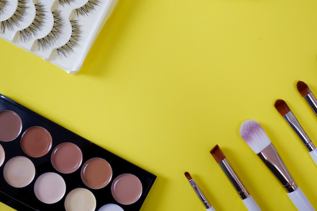 Top view of women's cosmetic on yellow background. Premium Photo