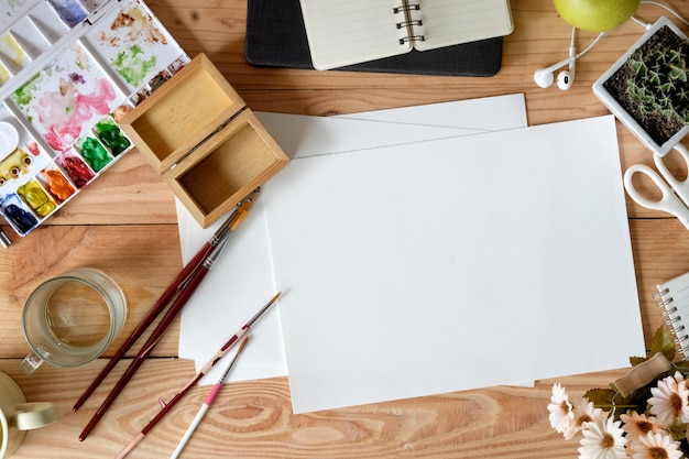 Top view wood desk of an artist with lots of stationery object. Premium Photo