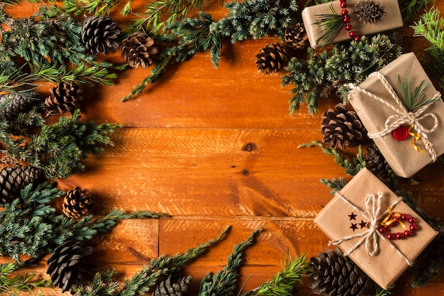 Top view wooden background with christmas tree cones frame Free Photo