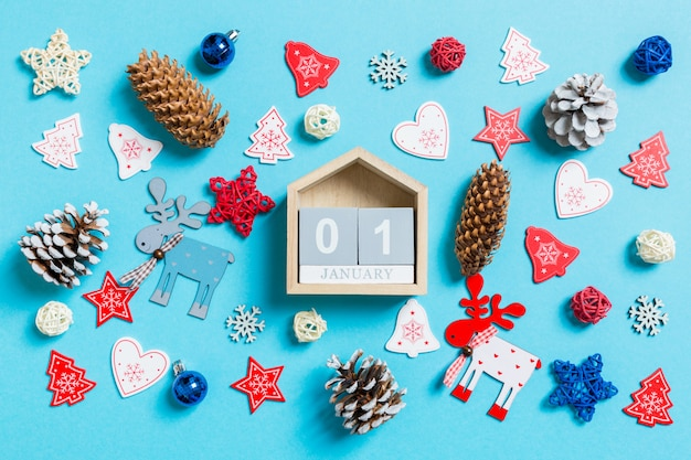 Top view of wooden calendar surrounded with new year toys and decorations on blue. Premium Photo
