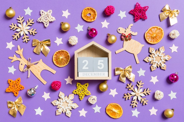 Top view of wooden calendar surrounded with new year toys and decorations on purple. Premium Photo