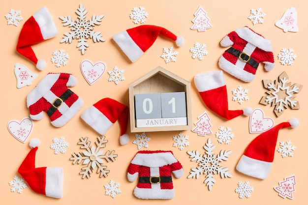 Top view of wooden calendar with christmas decorations and santa hats on orange. Premium Photo