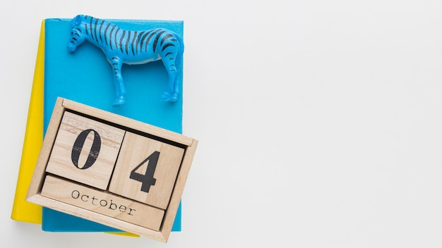 Top view of wooden calendar with zebra figurine and book for animal day Free Photo