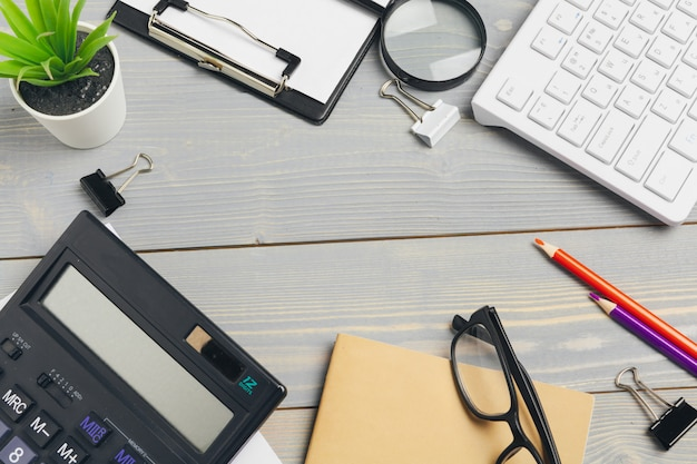 Top view of wooden desktop with glasses and stationery items close up. mock up Premium Photo