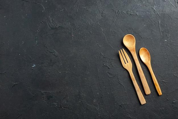 Вид сверху деревянная вилка и ложки на темном столе со свободным пространством Бесплатные Фотографии