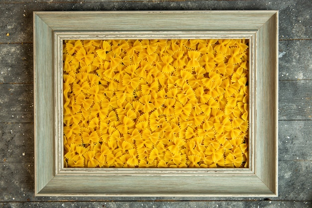 Top view of a wooden frame filled with raw pasta farfalle Free Photo