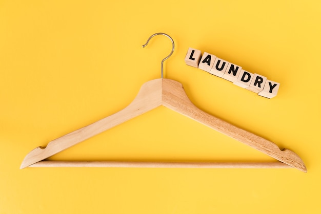 Top view wooden hanger with yellow background Free Photo