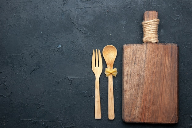 Top view wooden serving board wooden spoon and fork on dark table copy space Free Photo
