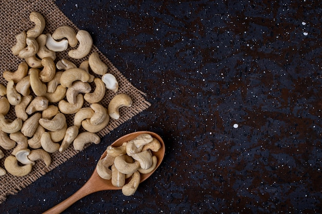 Top view of a wooden spoon with cashew on black background with copy space Free Photo