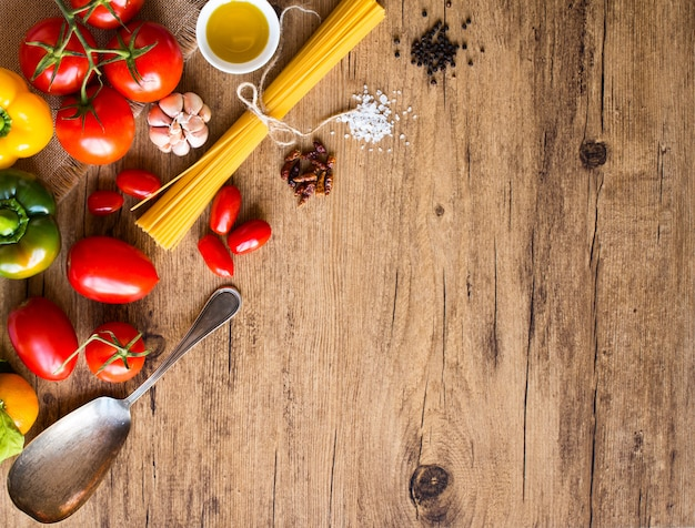 Top view of a wooden table full of italian pasta ingradients like peppers tomatoes olive oil basi Premium Photo