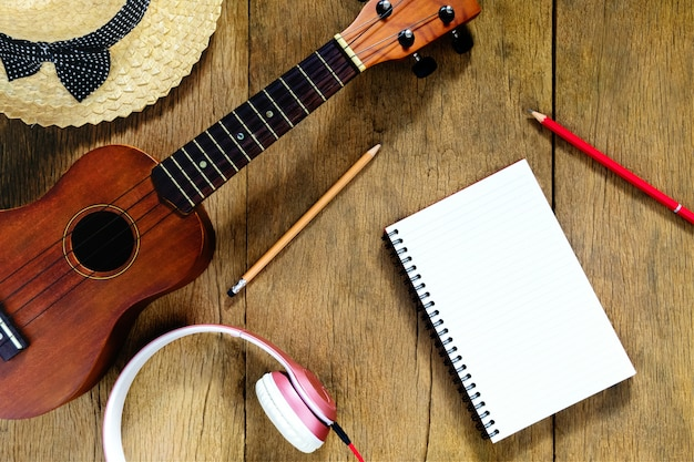 Top view wooden table, there are notebooks, pencils, hats, earphones, and ukulele Premium Photo