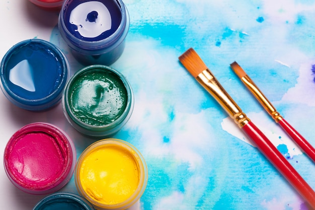 Top view of work process of watercolor paper pad, watercolor painting supplies and brushes Premium Photo