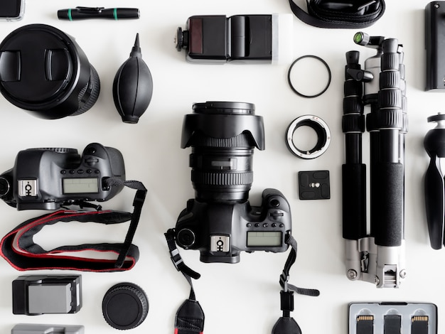 Top view of work space photographer with digital camera, flash, cleaning kit, memory card, tripod and camera accessory Premium Photo