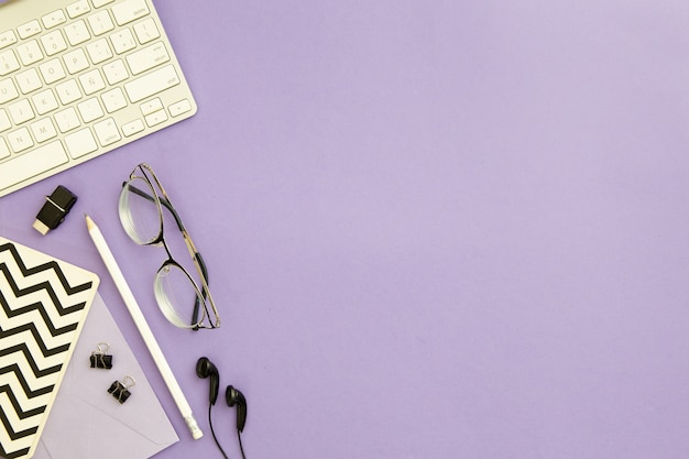 Top view workplace arrangement on purple background with copy space Premium Photo