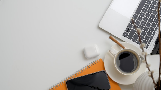 Top view of workplace with laptop, coffee cup, wireless device, decorations and copy space Premium P