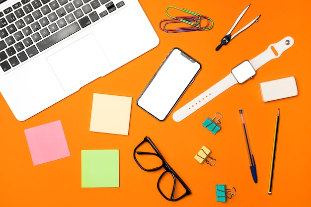 Top view workspace concept with orange background Free Photo