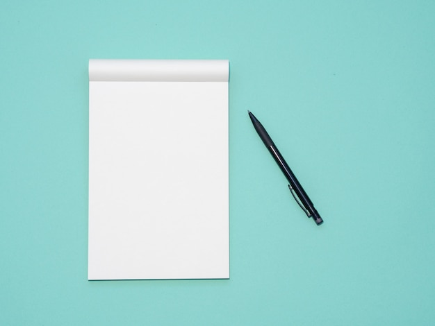 Top view workspace mockup on aqua background with open notebook and pen Premium Photo