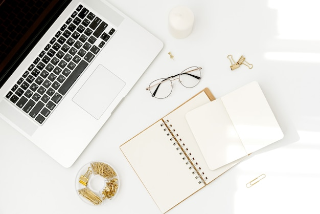Top view workspace mockup on white with notebook, accessories, candle and glasses Premium Photo