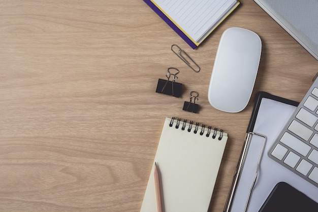 Top view of workspace with diary or notebook and clipboard, laptop, mouse computer, keyboard, smart phone, pencil, pen on wooden background Premium Photo