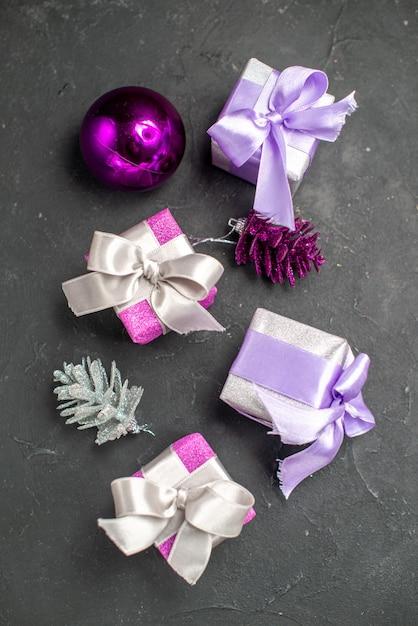 暗い孤立した表面のクリスマスの写真にリボンクリスマスツリーのおもちゃとピンクと紫のトップビューのクリスマスプレゼント 無料写真