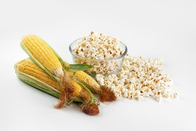 Una vista dall'alto calli gialli crudi con foglie verdi e popcorn freschi sulla scrivania bianca, mais color farina alimentare Foto Gratuite