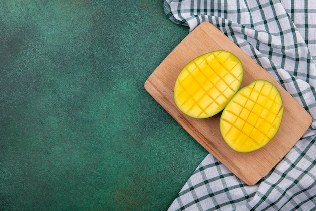Top view of yellow exotic fresh mango slices on a wooden kitchen board on checked tablecloth and green surface Free Photo
