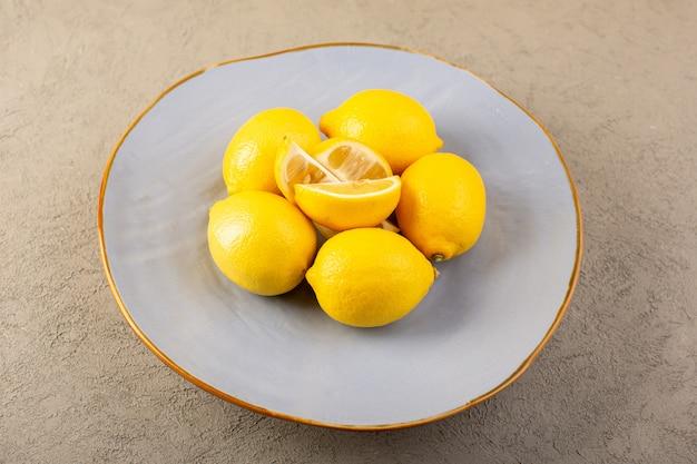 I limoni freschi gialli di una vista superiore interi morbidi e succosi e affettati dentro il piatto blu sul fondo grigio fruttifica il colore dell'agrume Foto Gratuite