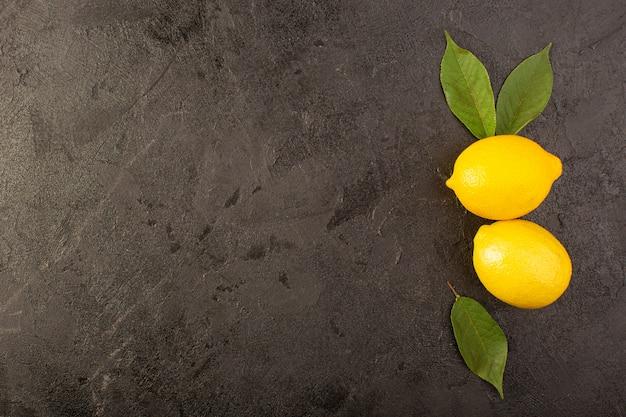 Una vista dall'alto giallo limoni freschi morbido e succoso intero e affettato con foglie verdi su sfondo scuro frutti di colore di agrumi Foto Gratuite