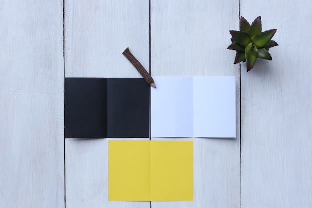 Top view yellow paper, white paper, black paper, pencil and flower pot on white wood floor Premium Photo