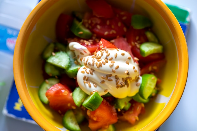 Top view on a yellow plate with a fresh vegetables salade, mayonnaise and rye grain focus Premium Photo