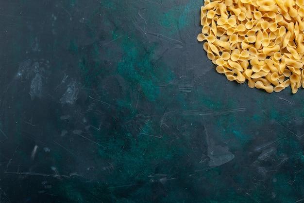 Вид сверху желтой сырой пасты итальянской пасты на темно-синем столе Бесплатные Фотографии