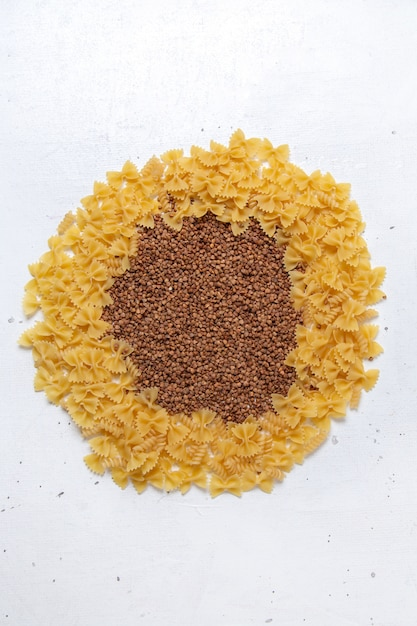 トップビュー黄色の生パスタ白い机の上のそばで少し形成されたパスタイタリア料理の食事 無料写真