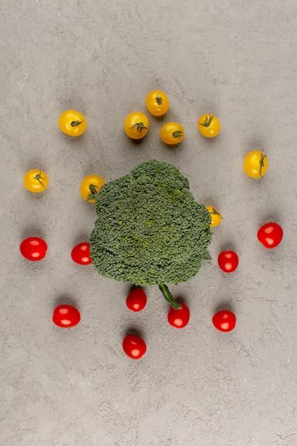 회색 배경에 녹색 브로콜리와 함께 상위 뷰 노란색 빨간 토마토 무료 사진