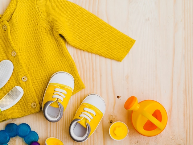 Top view yellow sweater with toys Free Photo