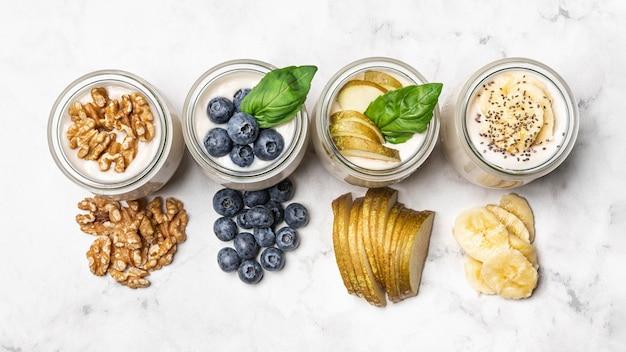 Top view yogurt with fruits and walnuts Free Photo