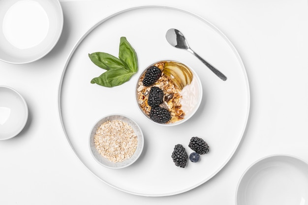 Top view yogurt with oats, fruits and honey on plate Free Photo