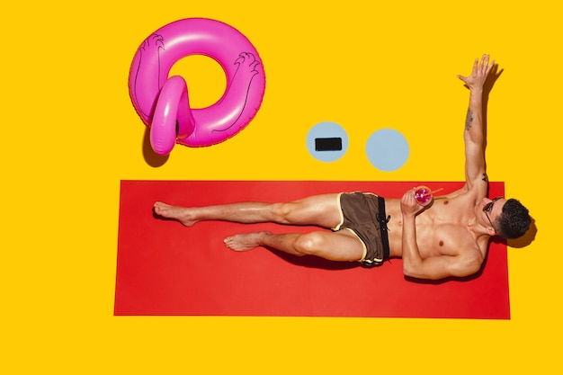 Top view of young caucasian male model's resting on beach resort on red mat and yellow Free Photo