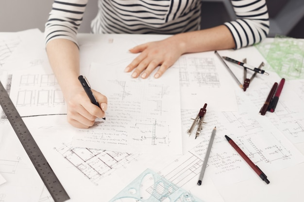 Top view of young good-looking freelance engineer wearing formal striped clothes working at comfortable bif table,making notes near blueprints to fix them later. Free Photo