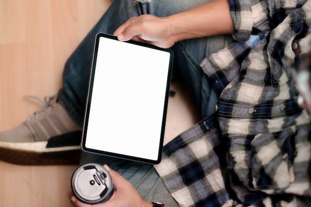 Молодой человек взгляд сверху используя таблетку пока сидящ на поле. Premium Фотографии