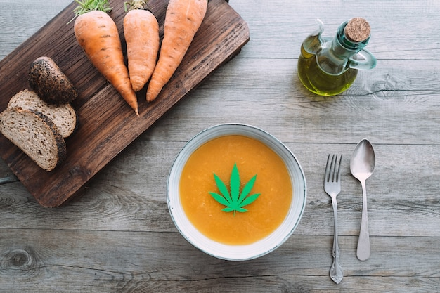 Top view of young woman eating carrot soup with marijuana oil and leaf inside Premium Photo