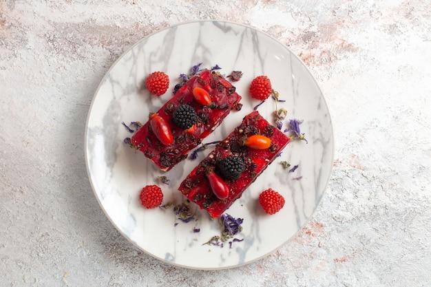 Вид сверху вкусные кусочки торта ягодный торт со сливками и ягодами на белом фоне Бесплатные Фотографии