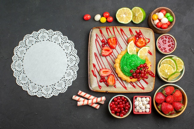 Top view yummy creamy cake with fruits on a dark background biscuit dessert sweet color Free Photo