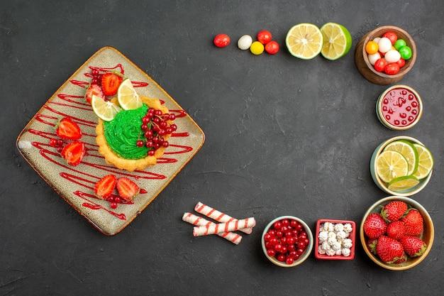 灰色の背景にフルーツとおいしいクリーミーなケーキの上面図デザートカラービスケット甘い 無料写真